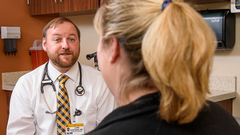 Luke Stephens, MD, visits with a patient at MU Health Care's family medicine clinic in Ashland.