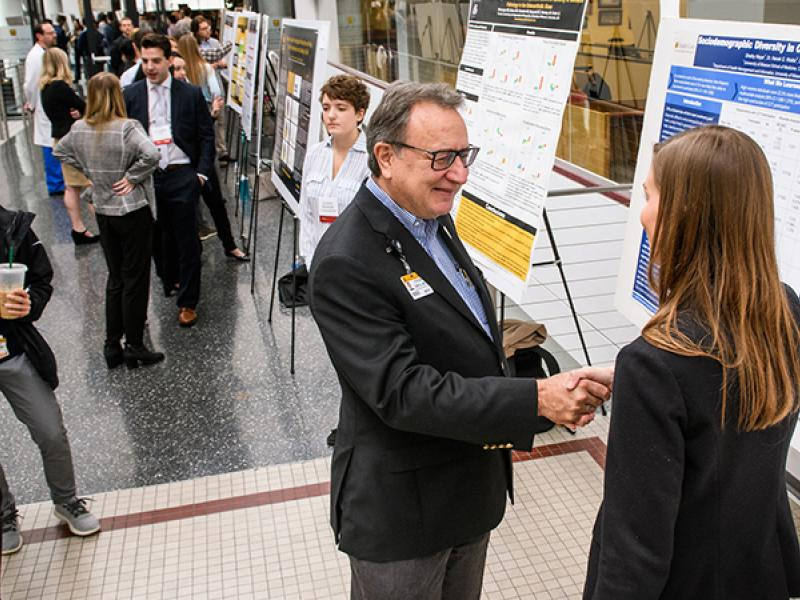 Dean Zweig reviewing a student's poster at Health Sciences Research Day