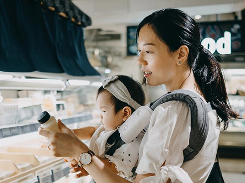 Asian woman grocery shopping with a baby